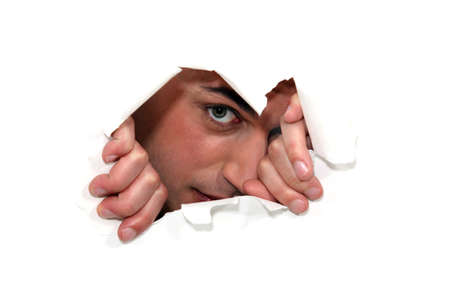 peeking: Man looking through a ripped paper wall. Stock Photo