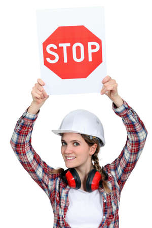 woman stop: Female builder holding stop sign