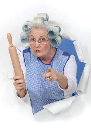 abuela: abuela con rulos amenazar a alguien con un rodillo