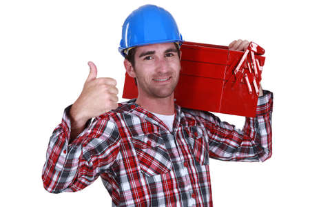 Handyman carrying tool box on shoulder and giving the go-ahead photo
