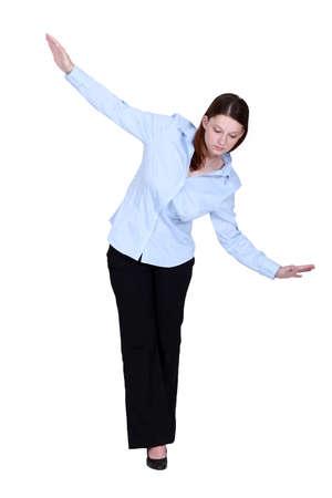 Woman walking an imaginary tightrope Stock Photo - 12091056