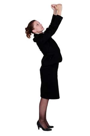 Businesswoman with raised arms photo