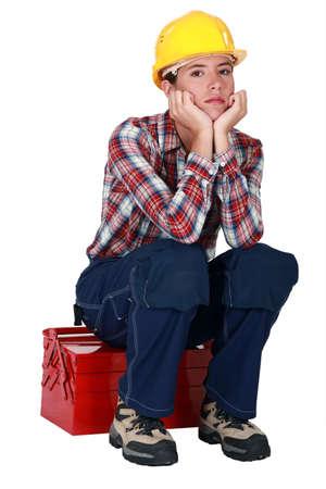 Bored female builder sat on tool box photo