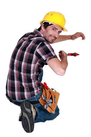 arrodillarse: Comerciante con una llave de tubo Foto de archivo