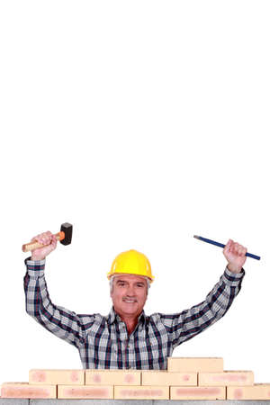 Tradesman holding a mallet and a chisel photo