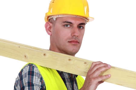 apathetic: Labourer carrying a wooden plank Stock Photo
