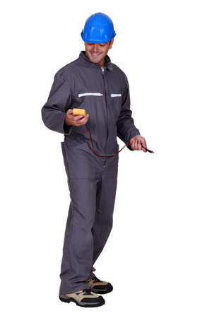coveralls: A tradesman holding a multimeter
