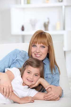 sitter: a 35 years old mother and her little girl lying down on a couch