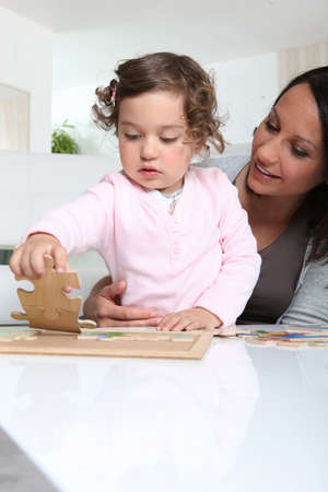 Madre e hija haciendo un rompecabezas photo
