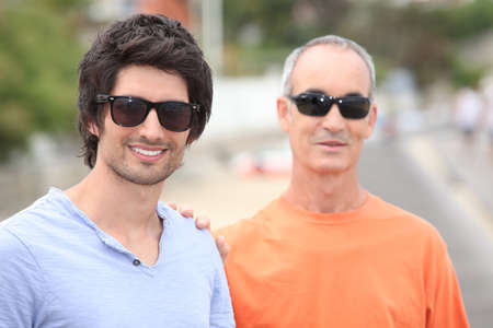 grown ups: Two men of different generations wearing sunglasses and t-shirts