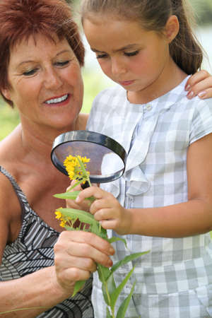 a 55 years old woman and a little looking a yellow flower with a magnifying glass photo