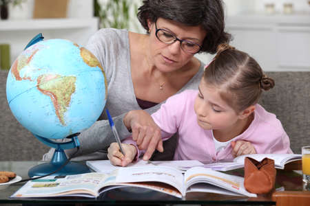 Mother teaching daughter geography photo