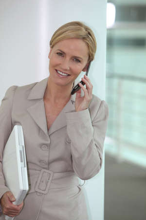 beautiful blonde woman: Smiling woman walking along carrying a laptop and cellphone Stock Photo