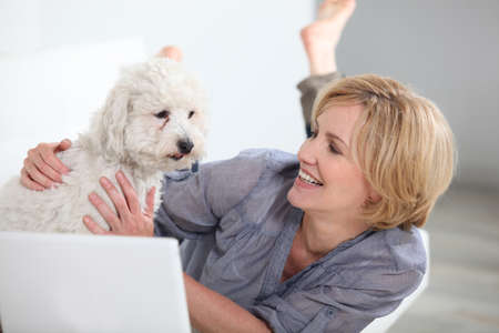 Woman smiling with dog and laptop photo