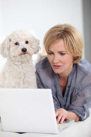Woman on laptop computer accompanied by small white dog photo