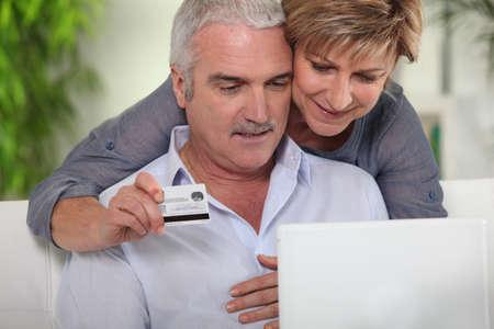 senior couple shopping on Internet photo