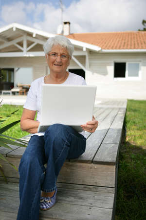 sinecure: Senior woman using a laptop outside her house