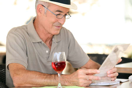 elderly gentleman seated in cafe drinking glass of red wine photo