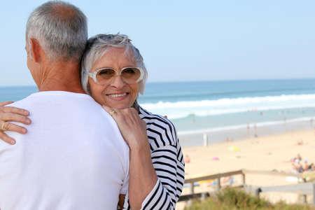 abuelos: una mujer mayor abrazando a su marido cerca del mar Foto de archivo