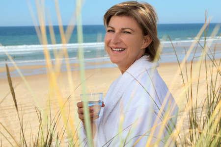 habitos saludables: Mujer con un vaso de agua en la playa Foto de archivo