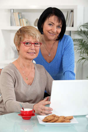 Two middle-aged women with laptop photo