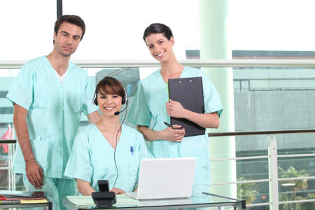 standard: two nurses standing and a nurse using a headset Stock Photo