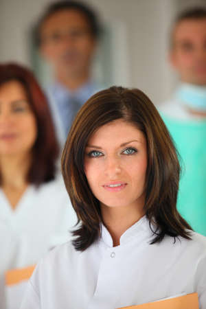 portrait of young female background with medical team in background photo