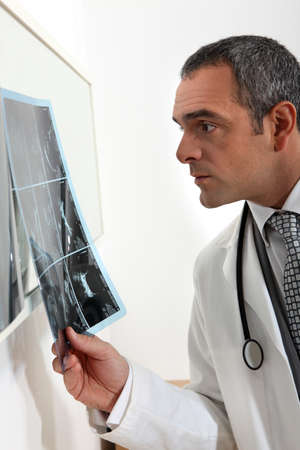 doctor examining x-ray photo