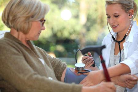 herida: la enfermera está comprobando anciana