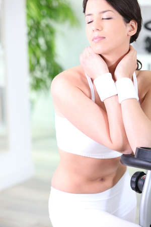 sportingly: Attractive brunette stood by cycling machine in gym