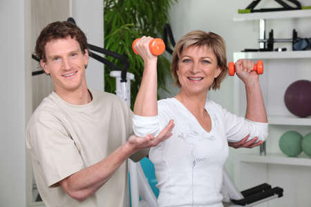 Woman being helped by her personal trainer photo