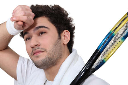 Tennis player wiping the sweat from his brow photo