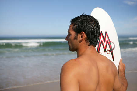 Man with a surfboard looking at the ocean photo