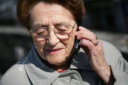 Elderly lady making a call outdoors Stock Photo - 12091805