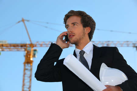 businessman on a construction site talking on his cell phone photo