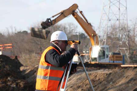 surveyor: perito en el sitio de construcción con una grúa en el fondo