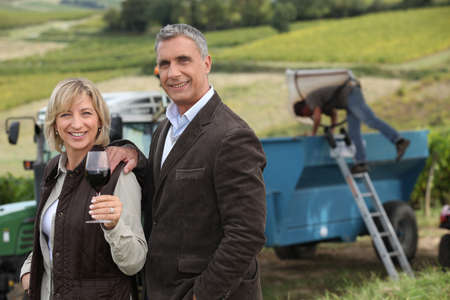 hand on shoulder: Farmer and wife in front of equipment
