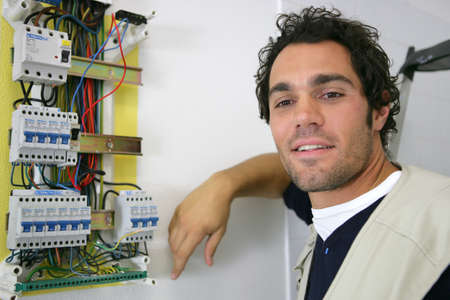 contador electrico: electricista joven posando cerca de medidor de electricidad