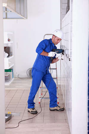 commercial activity: Tradesman using a power drill Stock Photo