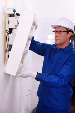 fuse box: Man inspecting fuse box Stock Photo