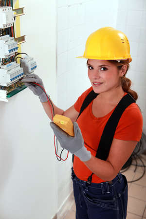 fusebox: Female electrician taking reading form fuse box