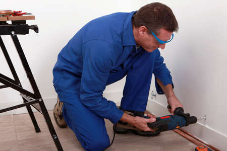 safe water: Plumber fixing copper pipe to wall