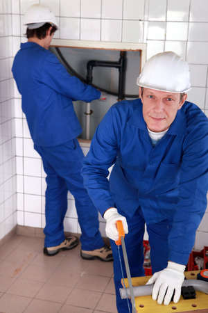 Two male plumber working together photo