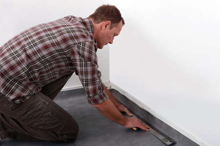 kneeling man: Tradesman laying down linoleum flooring