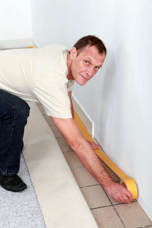 kneel down: Man making preparations to fit new carpet