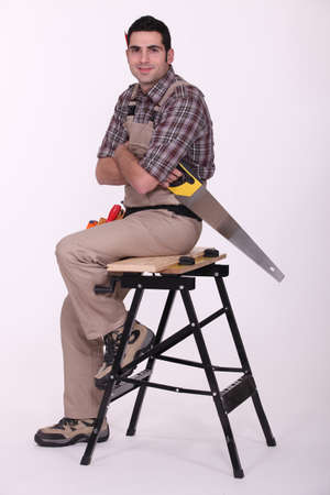 Laborer with saw sitting on a workbench photo
