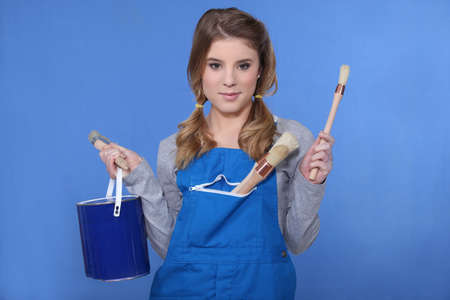 Woman holding paint brush and paint pot photo