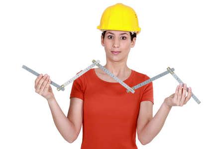 servicewoman: craftswoman holding a meter ruler