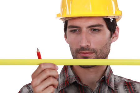 tools belt: Man in a hardhat with a pencil and measure Stock Photo