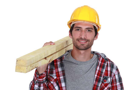 Carpenter carrying planks of wood over shoulder photo